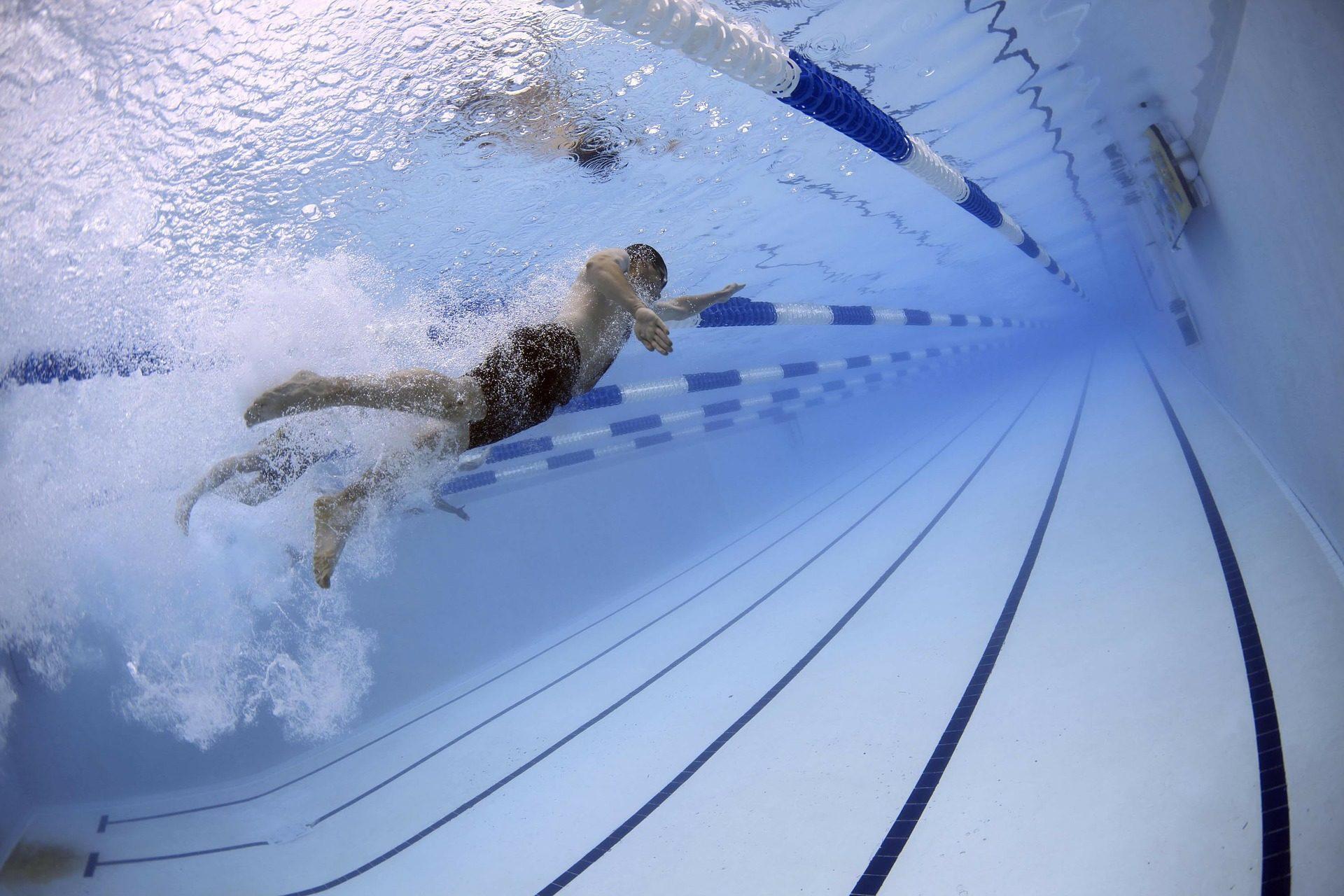 das Bild zeigt einen Mann beim Scwimmtraining in einem großen Schwimmbecken