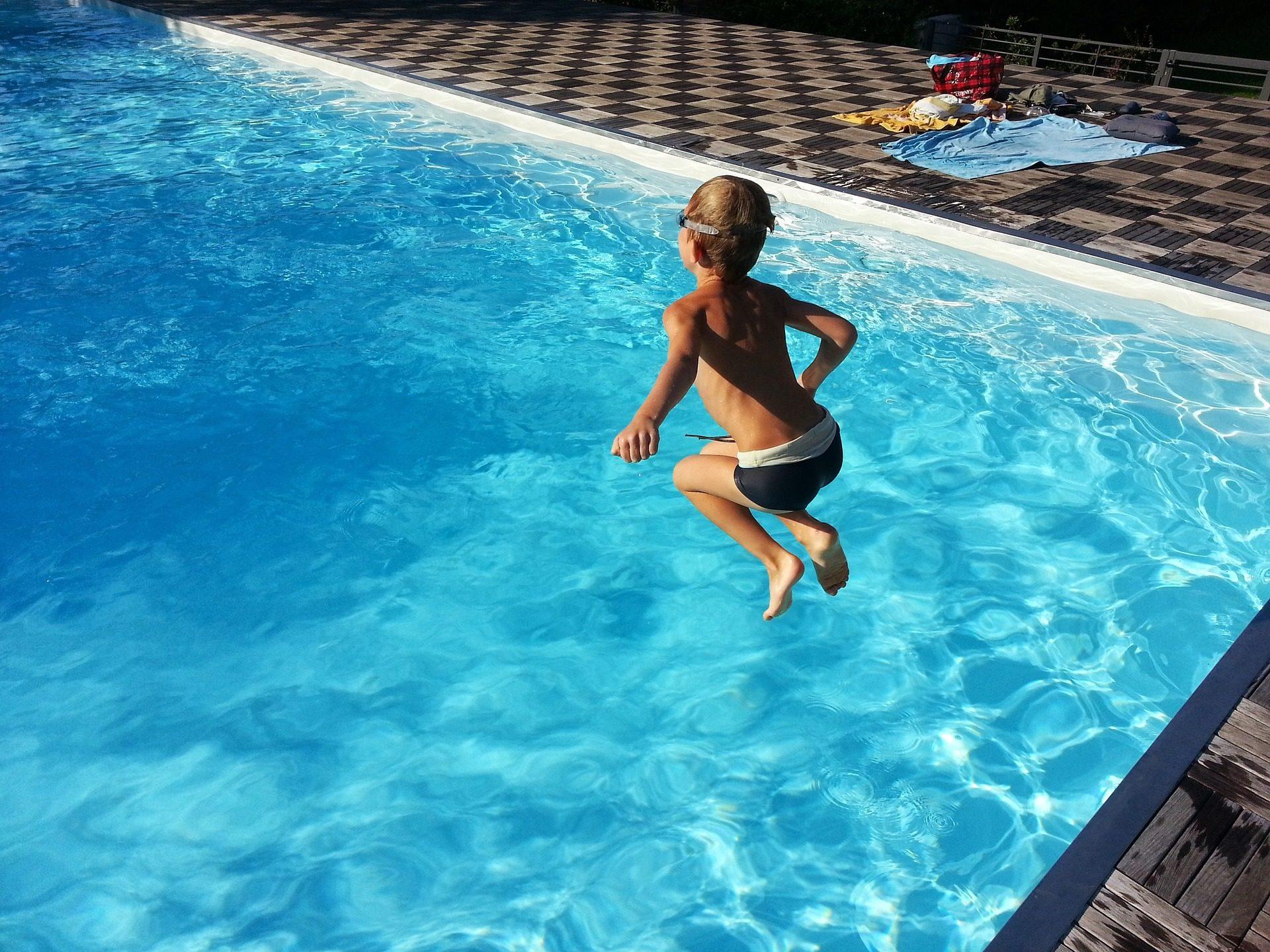 das Bild zeigt einen kleinen Jungen, der in einen Folienpool von Schwimmbad Schall springt