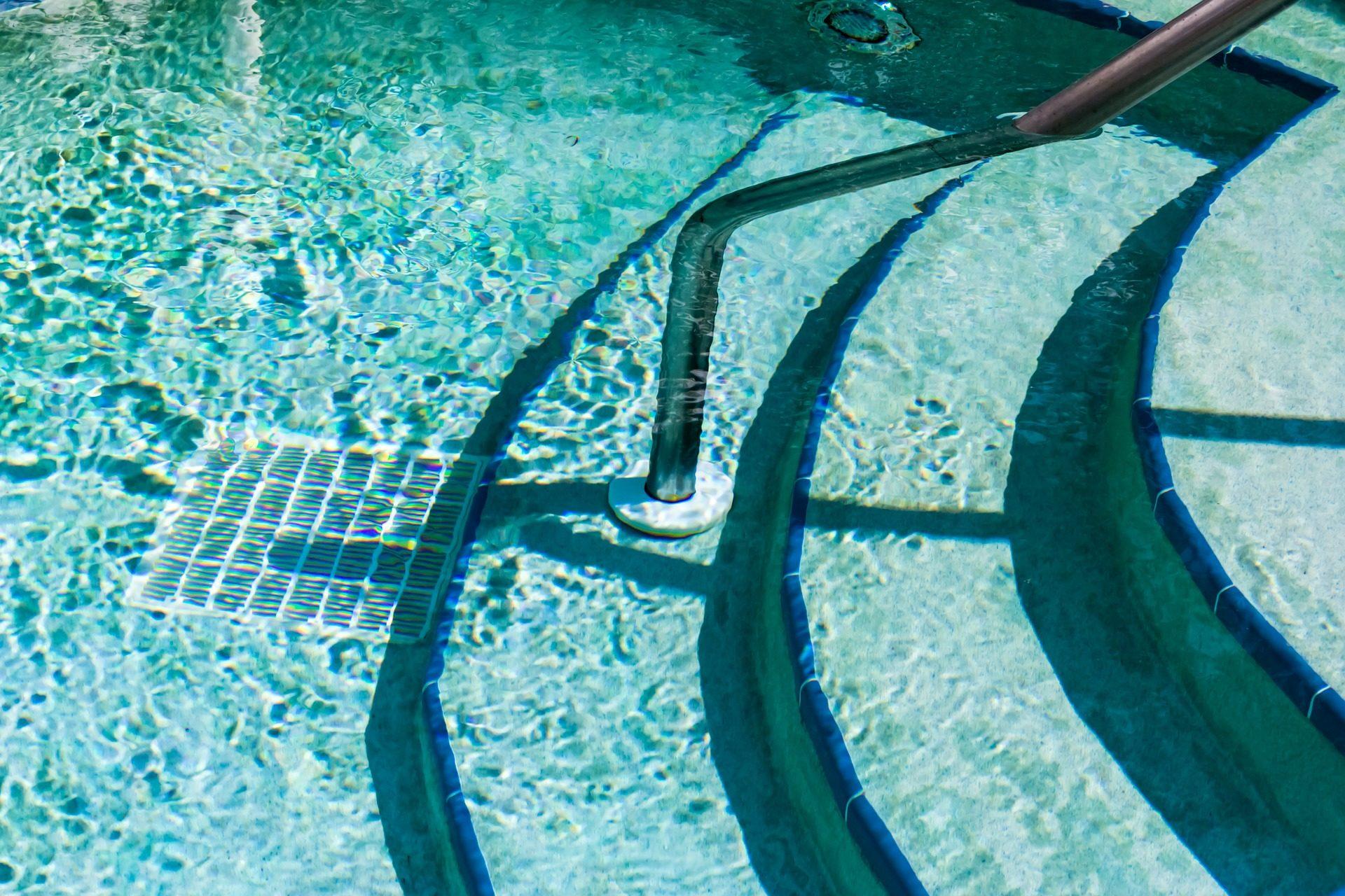 das Bild zeigt eine Pool Treppe Freiform mit Handlauf in der Mitte