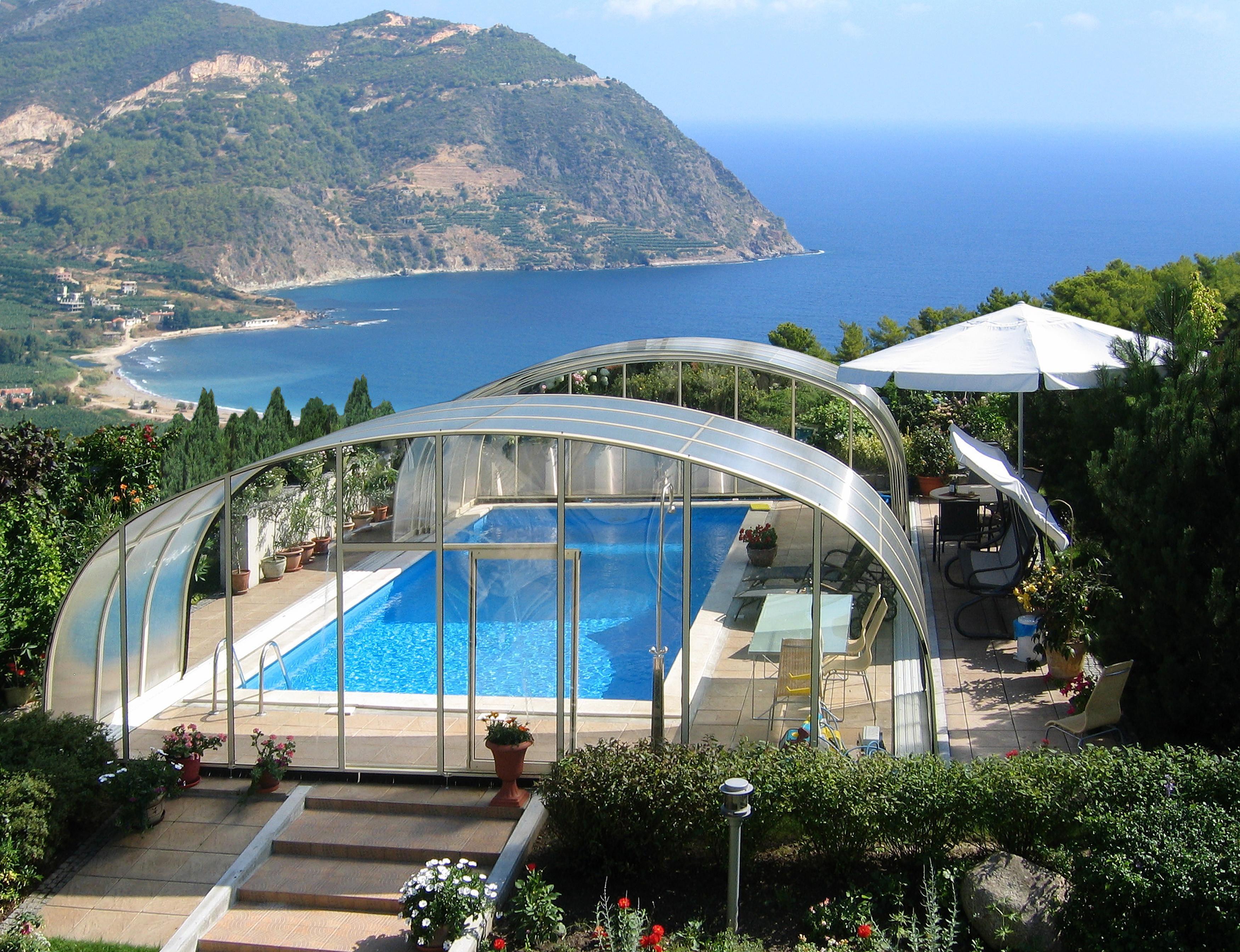 das Bild zeigt einen großen Swimming Pool mit halb aufgeschobener Überdachung und mit Blick aufs Meer